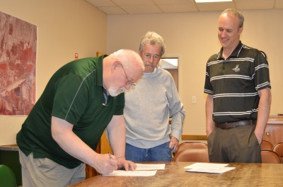 BARBARA ANNE GREENE Basin Mayor Dennis Peters signs the land agreement with Big Horn County School District Four. Watching are councilman Bill Stoelk and District Business Manager Andy DeGraw.